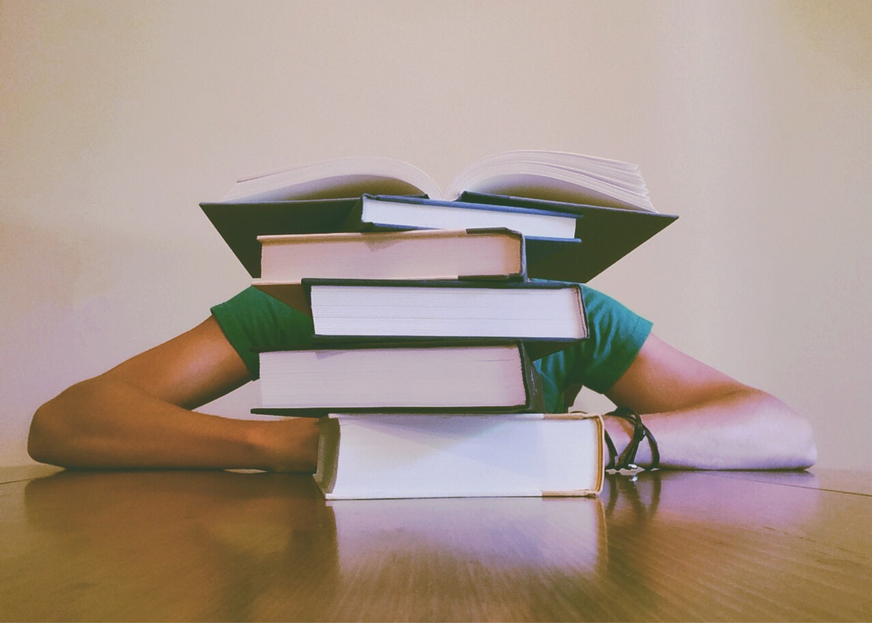 stack of books with person hiding behind.