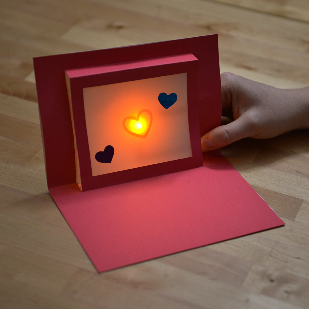 Hand holding light up pop up card with heart design