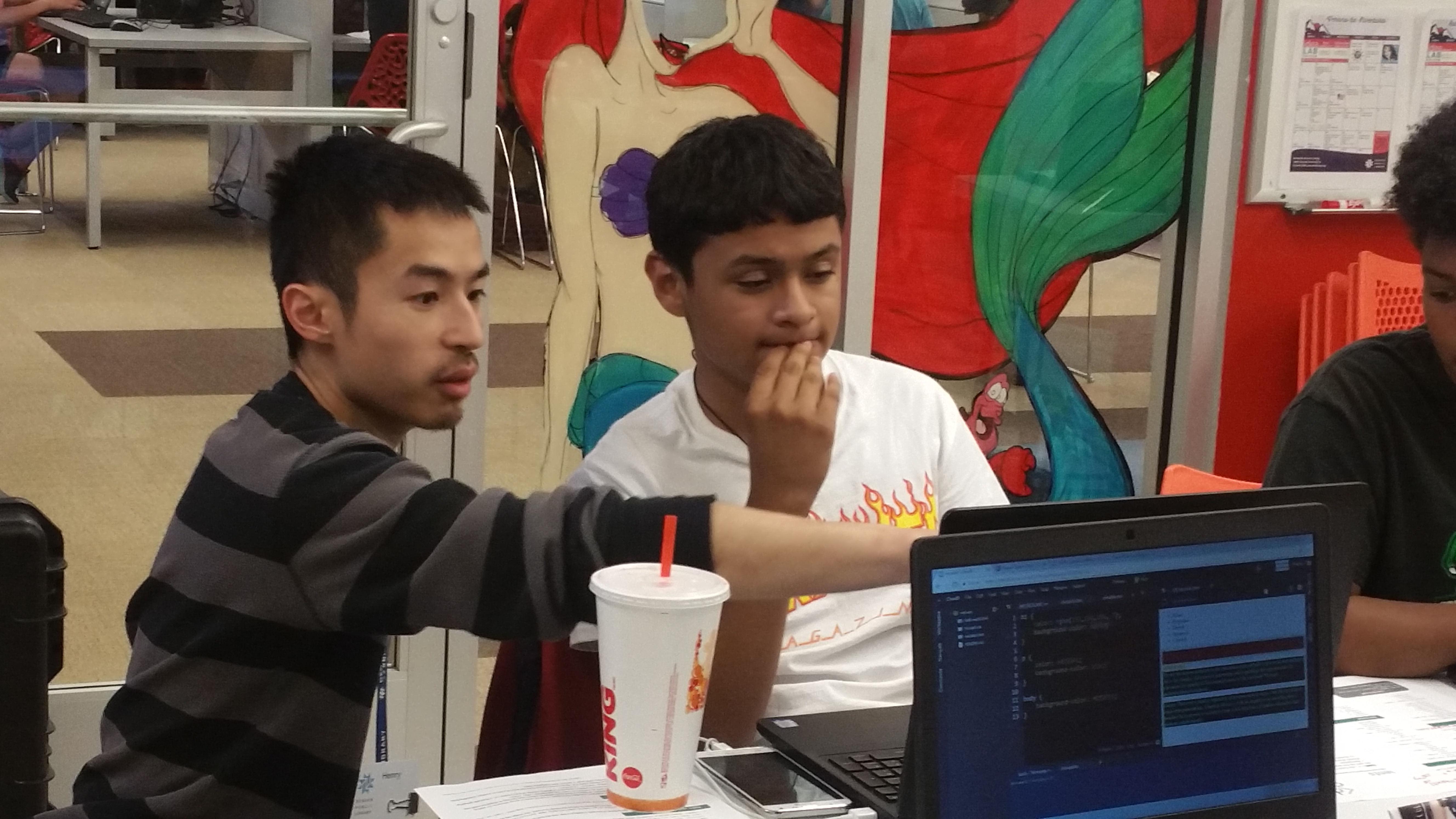 A mentor helping a participant at the 2017 DevCamp in the Montbello Branch Library