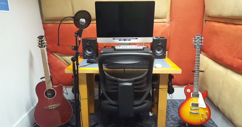 Recording studio computer, speakers, microphone, and guitars