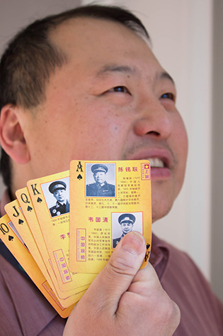 Photograph of a man holding several playing cards featuring pictures of generals and marshals on them