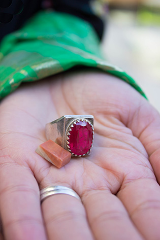Photograph of a woman's hand holding a ring with a pink jewel and a small stone