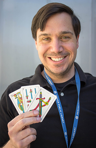 Photograph of a smiling man holding playing cards