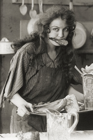 A black and white still from the movie The Ocean Waif showing a woman holding food in her mouth while she carries a tray.