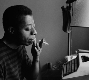 A black and white photograph of James Baldwin wearing a striped shirt, smoking a cigarette, and sitting at a typewriter.