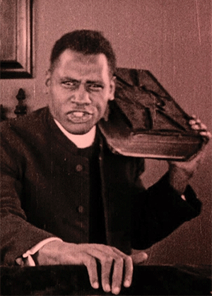 A sepia still from the movie Body and Soul showing a man holding a bible on his shoulder and speaking passionately.