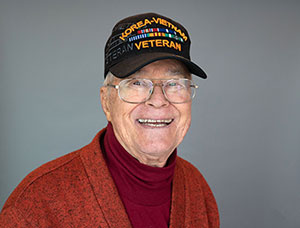 "Older man wearing glasses and a ""Korea - Vietnam Veteran"" hat looking at the camera and smiling"