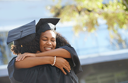 Two people in graduation caps and gowns hugging