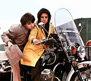 An image from the film Harold and Maude showing a woman and a boy riding a motorcycle