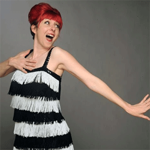 Photograph of Honey Touché with bright red hair and wearing a black and white fringed dress.