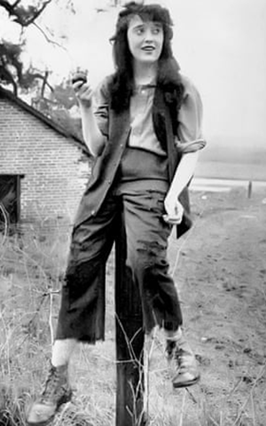 A black and white still from one of Mabel Normand's shorts showing a girl sitting on a fence wearing work clothes and boots and holding an apple.