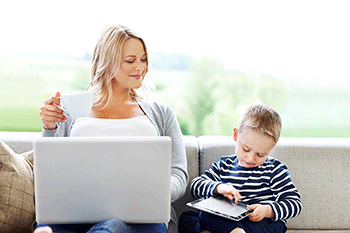 A woman with a laptop and a young boy with a tablet sit together on a sofa