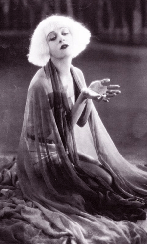 A black and white still from the movie Salomé showing a woman with light hair and flowing clothing kneeling on the ground with her hands outstretched.