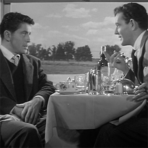 A still from the movie Strangers on a Train showing two men sitting face to face across a table on a train car with outdoor scenery in the background.