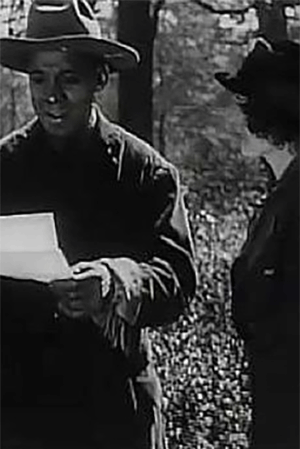 A black and white still from the movie The Symbol of the Unconquered showing a man in a cowboy hat reading a letter while a woman listens.