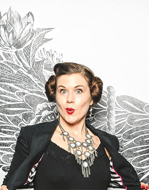 A photograph of Vieux Carre with 1940s style hair, standing in front of a floral backdrop.