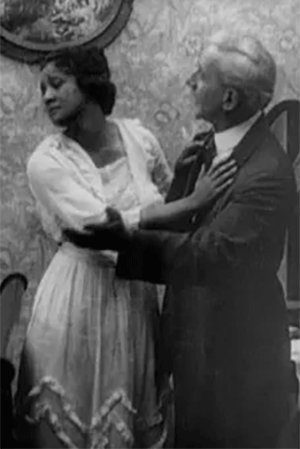 A black and white still from the movie Within Our Gates showing a woman pushing away from a man who has his arms around her.