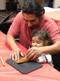 Man creating art with young child in Plaza