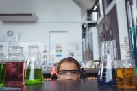 Young girl with safety goggles on looking at science experiments