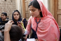 Photograph of a female doctor treating a patient in Pakistan.