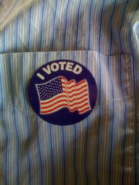 "Sticker on shirt reading ""I voted"" with an American flag"