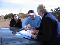 Three people lean on the hood of a truck, looking at a folder of papers
