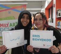 Photograph of DPL staff members holding welcoming signs in Arabic and Spanish