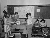 "Source description: Boy and girl students cast ballots at Morey Junior High School at 840 East 14th (Fourteenth) Avenue in the Capitol Hill neighborhood of Denver, Colorado. A bookcase serves as the voting booth. Shows wooden desks and a blackboard with a map of the United States. Writing on the board reads: ""Oct. 16, 1940. Miss Wolfe. Comm[?]. Boys. Oct. 14 16 [cents]. Oct [?] 11 [cents]."""