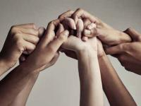 Photograph of a group of people's hands holding on to each other