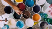 Hand with a paintbrush reaching over multiple cups of colorful paint