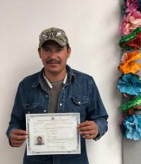 Photograph of a man with naturalization certificate.