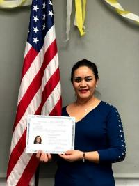 Photograph of woman with naturalization certificate