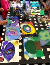 Table with kids painting different pictures