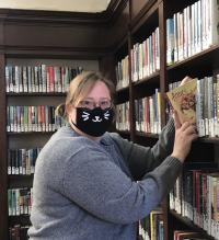 An attractive librarian wearing a face mask shelves a book in the Park Hill Branch Library