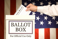 Hand placing ballot in box with American flag in the background.