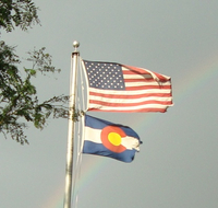 U.S. and Colorado flags flutter from the same flagpole. Denver Library image