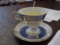 A delicate, pedestaled teacup just filled with lightly scented soy wax.