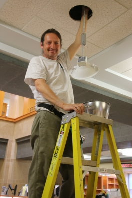 Michael Brodsky works on replacing overhead lamps in the Central Library