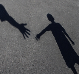 Helping hand - shadow of hands reaching for each other
