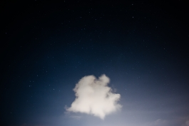 photograph of a single cloud in a starry night sky