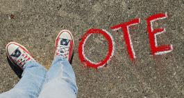 "The word ""Vote"" painted on a sidewalk, with two feet in American Flag Converse making the word's initial letter."