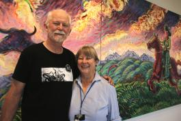 Warren and Deb Wadsworth pose in front of one of the library's paintings