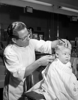little boy getting his first haircut - black and white photo