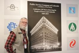 Western History Reference Librarian Roger Dudley poses by the Public Service Co. Exhibit poster in the Central Library