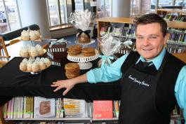 David Bondarchuck poses in the library with some of his famous cookies and cupcakes