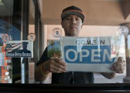 "Photo showing a man hanging an ""open"" sign in his business. Another sign reads ""Veteran owned business."""