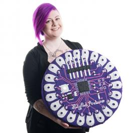 photo of Angela Sheehan holding a large embroidered version of a LilyPad Arduino