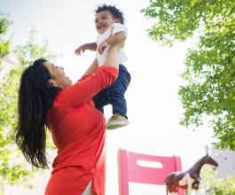 Woman holding smiling young child up in the air.