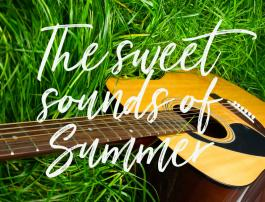 "A guitar in green grass with words, ""The sweet sounds of summer."""