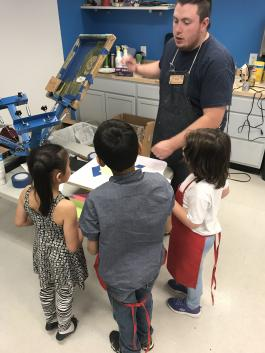 Hugh Scott, Maker in Residence at the Hampden Branch Library, demonstrates a screen press to a group of kids.